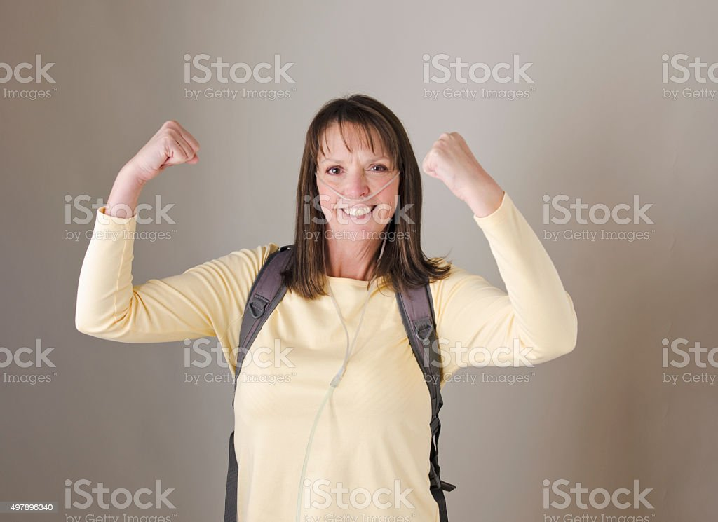 Lady on wearing oxygen equipment flexes her muscles. stock photo