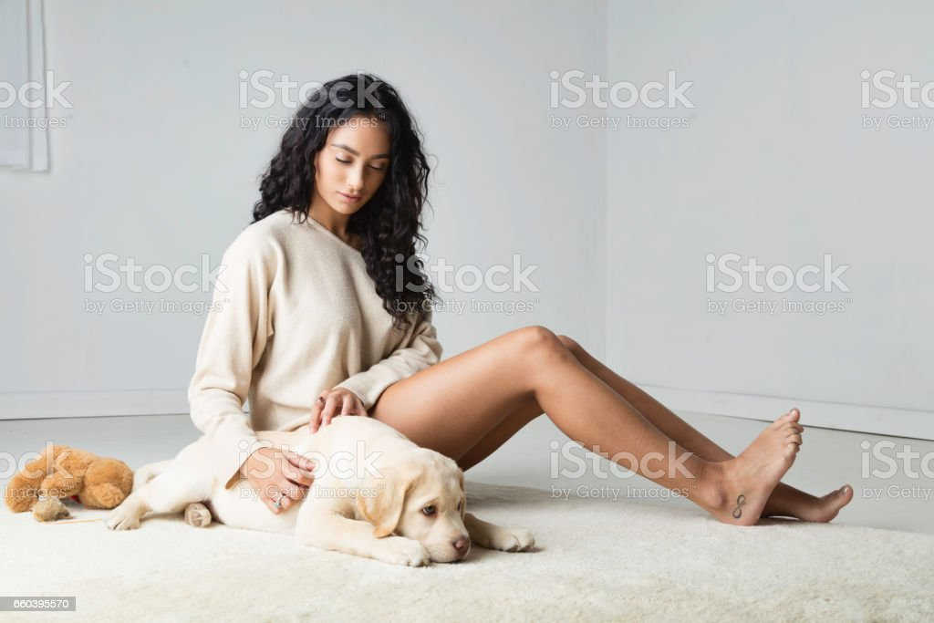 Lady playing with her Labrador puppy stock photo
