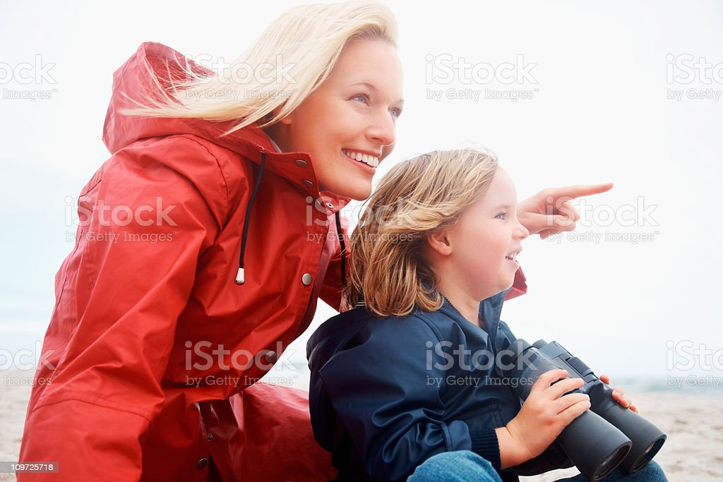 Lady pointing at something to girl as she holds binoculars royalty-free stock photo