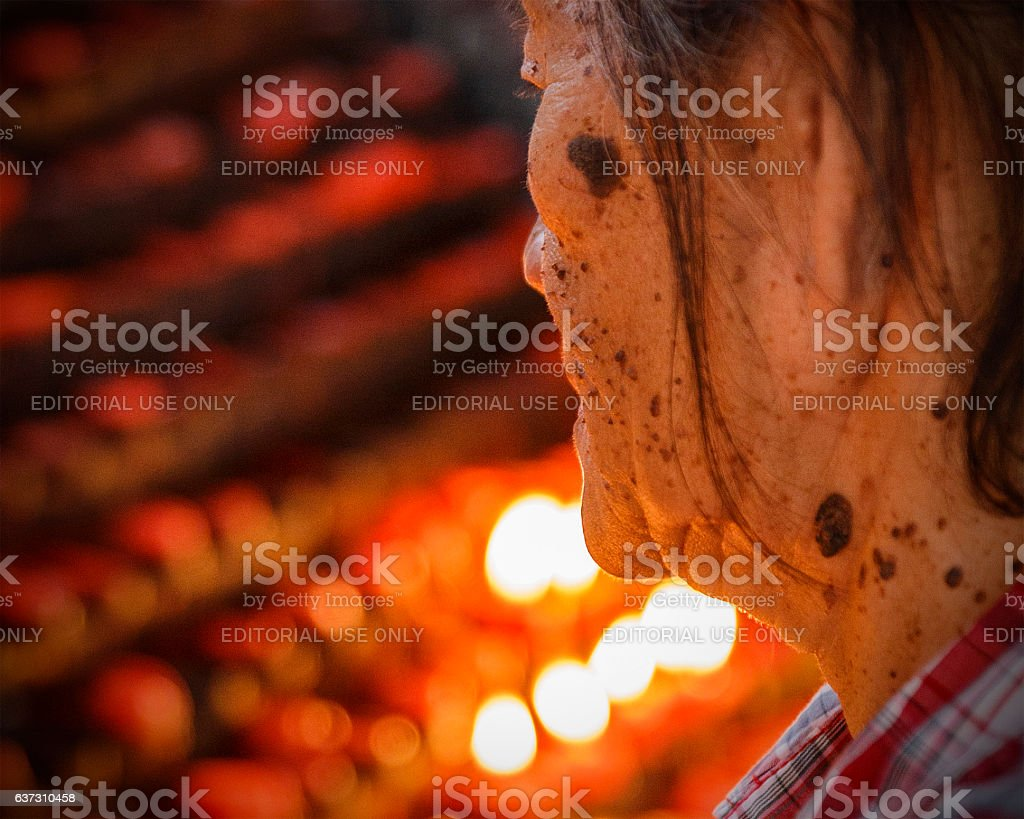 lady praying in fron of the offering candles stock photo