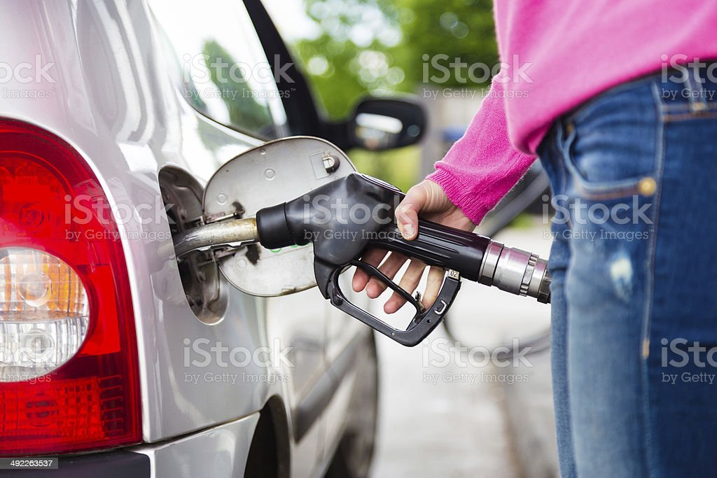 Lady pumping gasoline fuel in car at gas station. stock photo