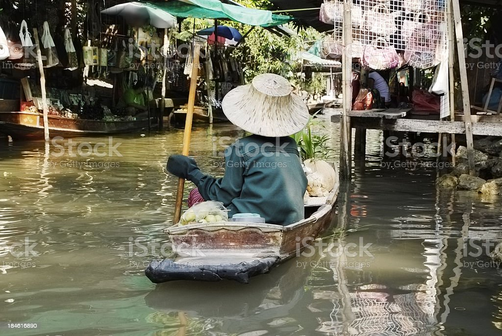 Lady punting boat through floating market in Thailand royalty-free stock photo