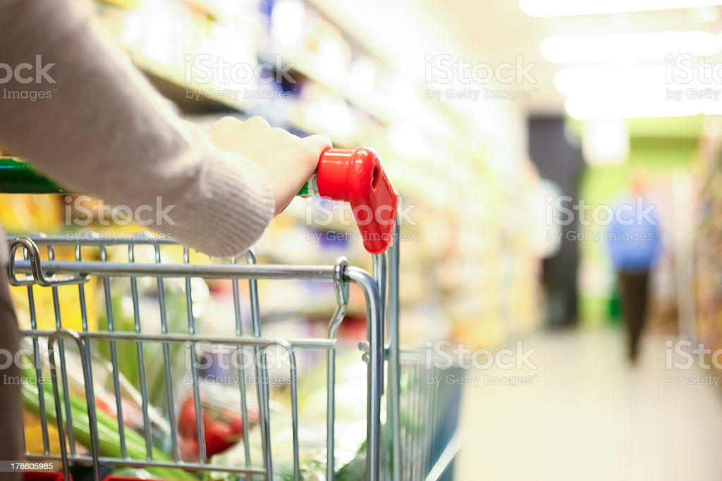 A lady pushing a shopping cart in a supermarket stock photo