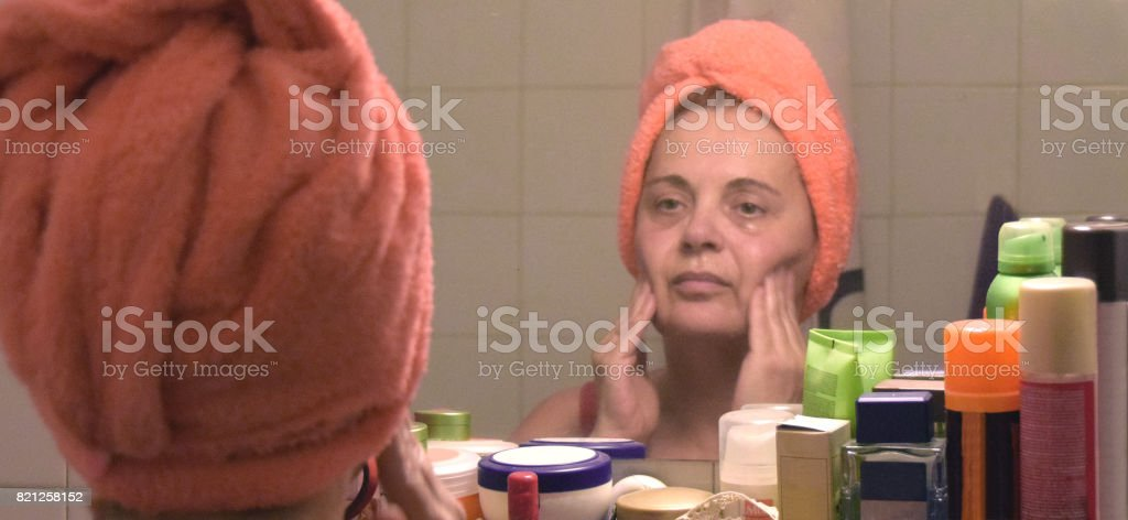 Lady puts a regenerative cosmetic mask on her face