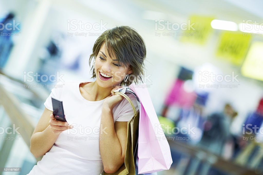 Lady reading a text message while at the shopping mall royalty-free stock photo