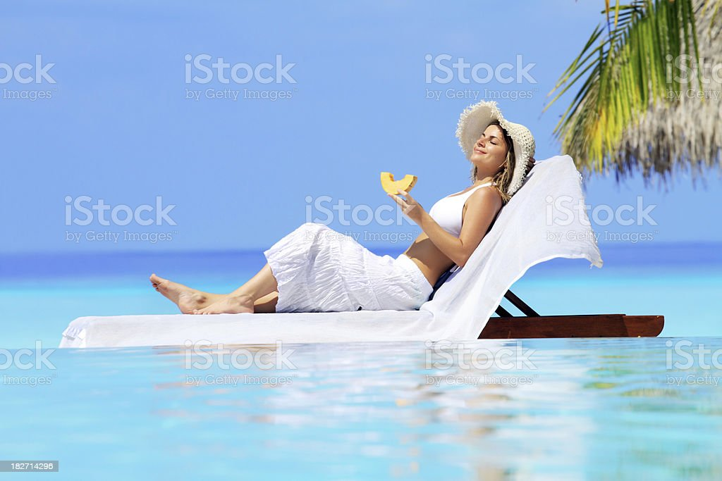 Lady relaxing in the chaise lounge on a exotic resort. stock photo