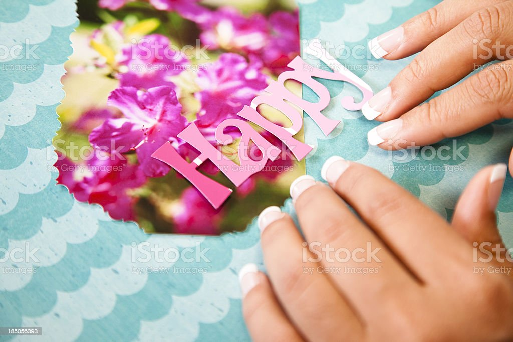 Lady scrapbooking, arranging the word happy on a photograph. royalty-free stock photo