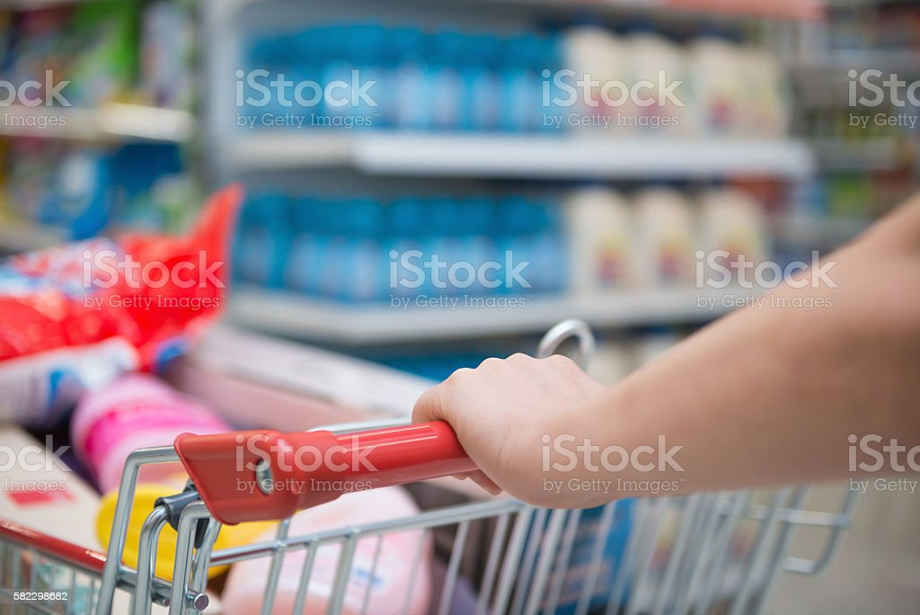 lady shopping with a full filled cart in a supermarket stock photo