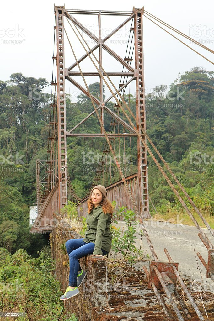 Lady Sitting at the Border of an old Steel Bridge stock photo