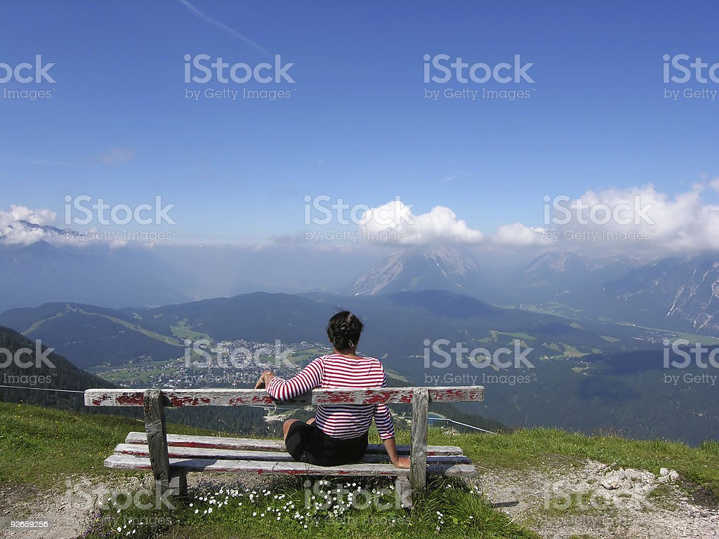 Lady sitting on wooden bench viewing the Alpines royalty-free stock photo