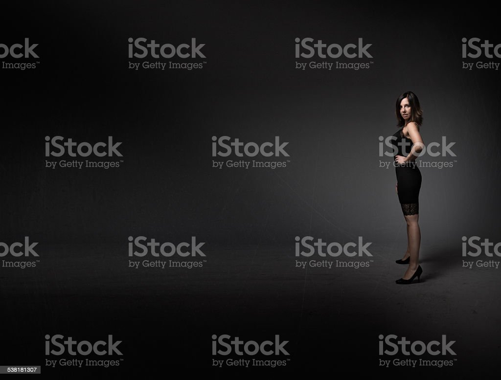 lady standing in a dark empty room stock photo