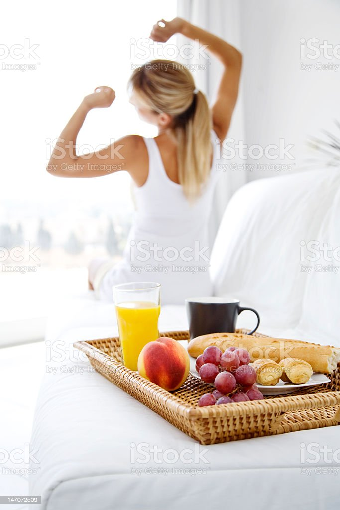 Lady stretching in morning with breakfast in bed royalty-free stock photo