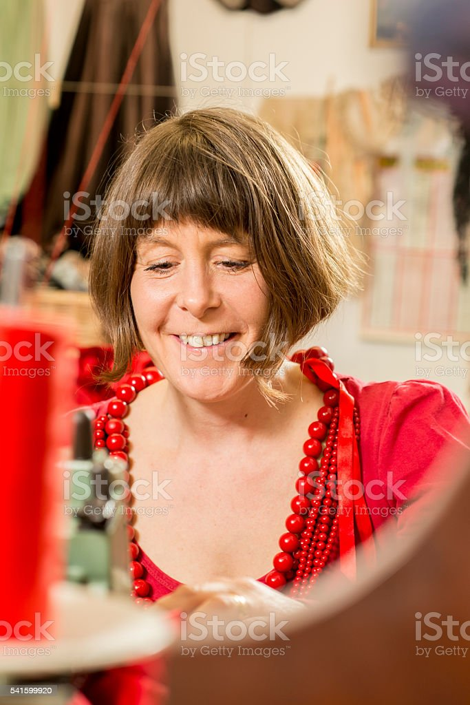 Lady Tailor in Red Dress and Necklace Working stock photo
