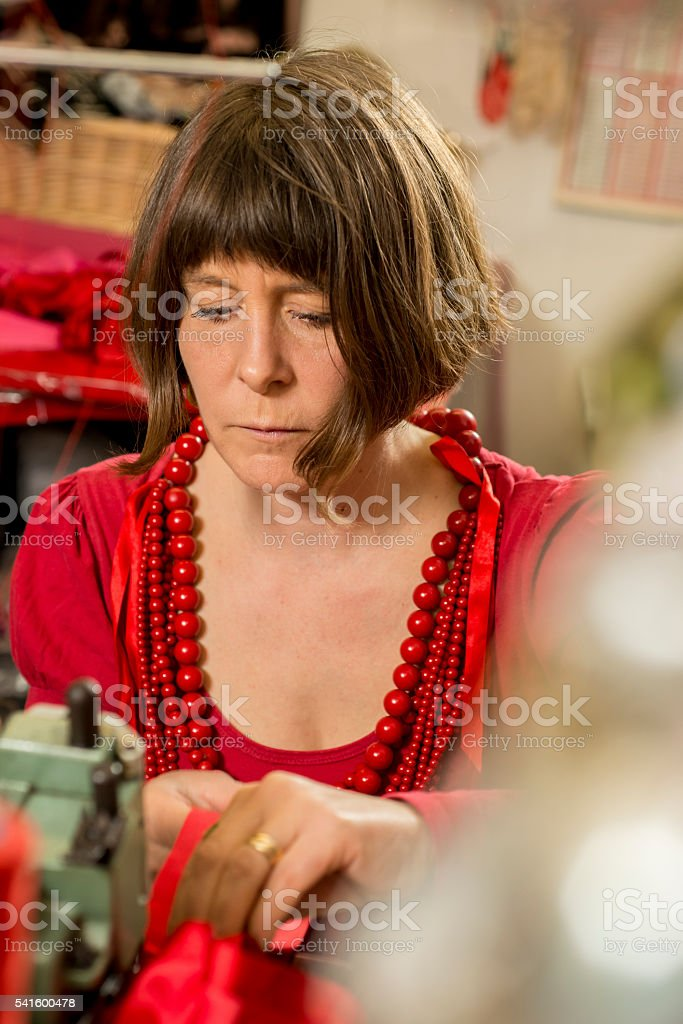 Lady Tailor in Red Dress and Necklace Working Seriously stock photo