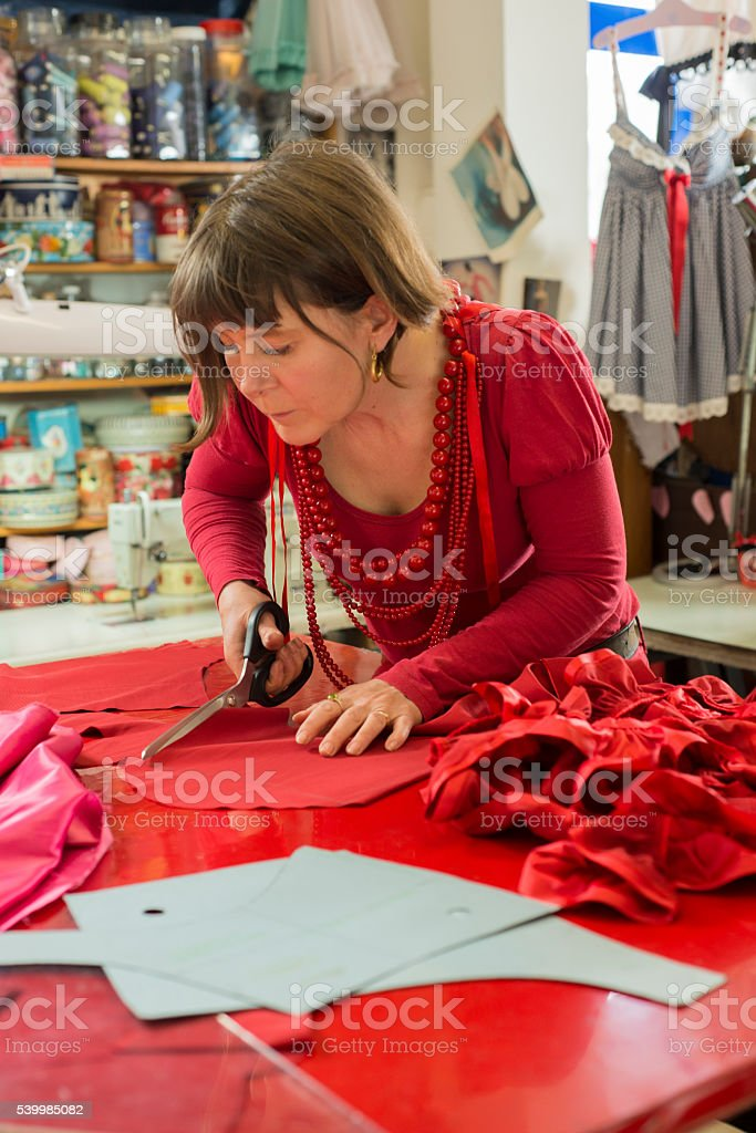Lady Tailor Trimming Red Cloth with Shears stock photo