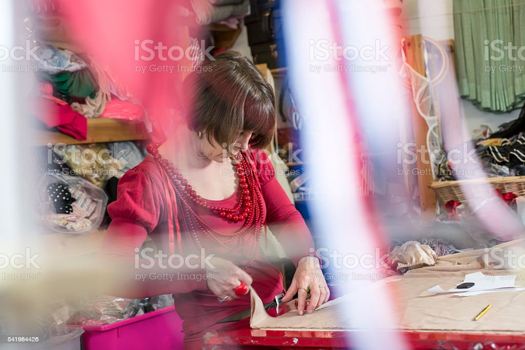 Lady Tailor Working on Cloth on a Cutting Table stock photo