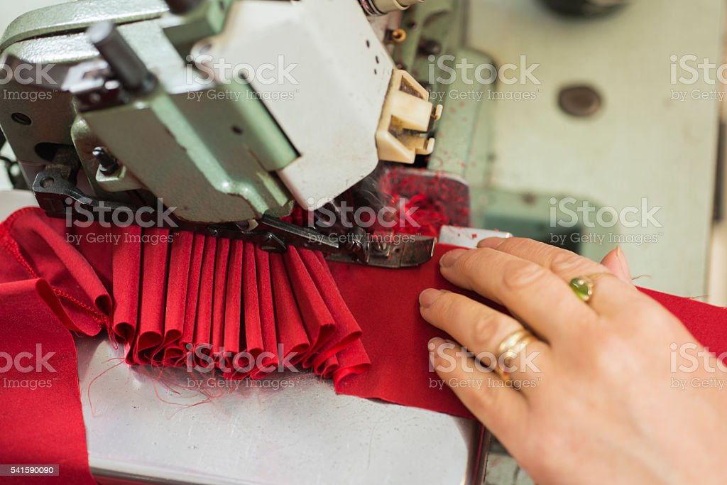 Lady Tailor's Hands Stitching Red Cloth on Sewing Machine stock photo
