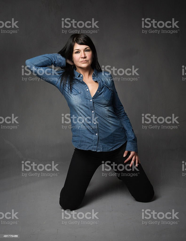 lady touching hair while on knees stock photo