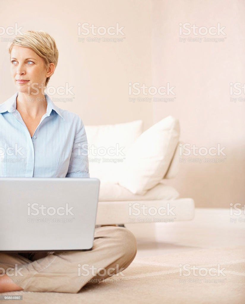 Lady using a laptop at home looking away royalty-free stock photo