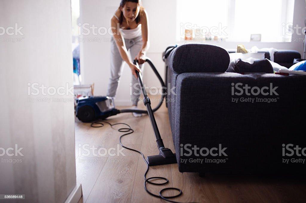 Lady vacuuming living room stock photo