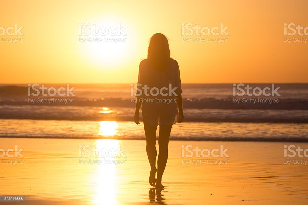 Lady walking on sandy beach in sunset. stock photo