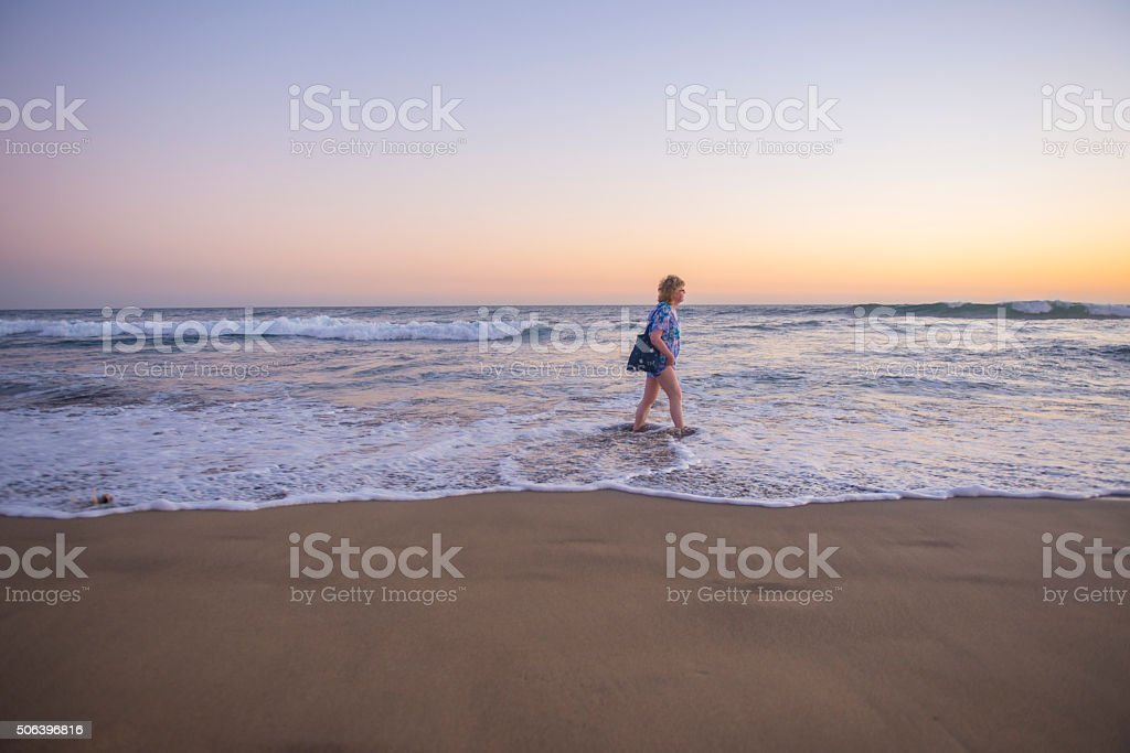 Lady walking on the waters edge stock photo