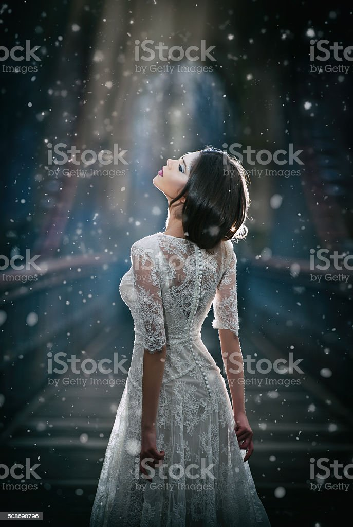lady wearing white dress enjoying the beams of celestial light stock photo