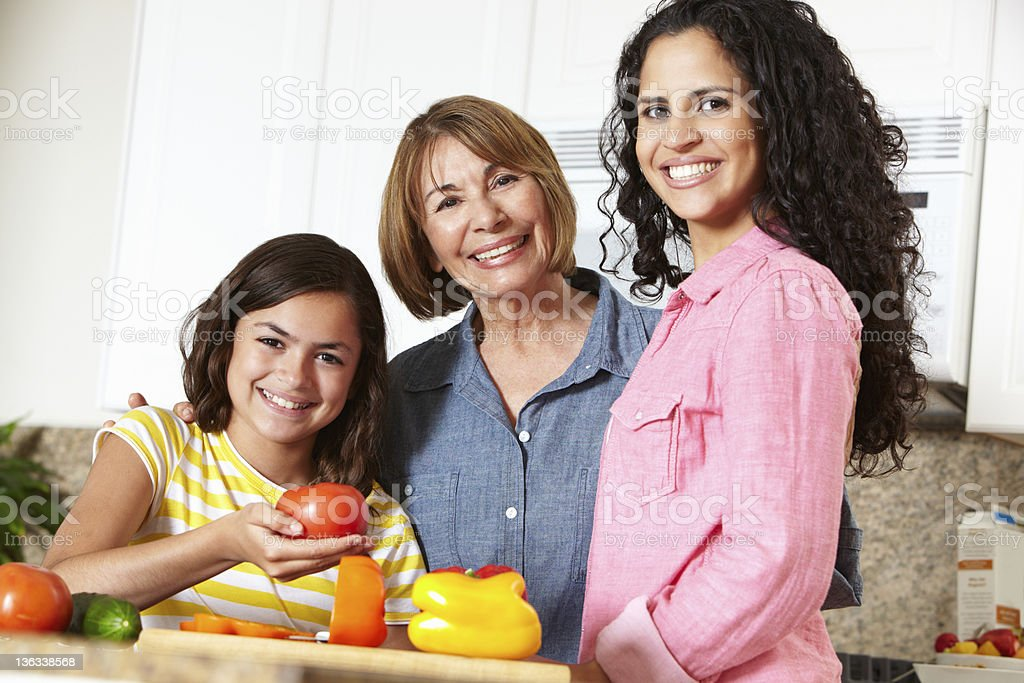 A lady with her daughter and mother preparing a meal stock photo
