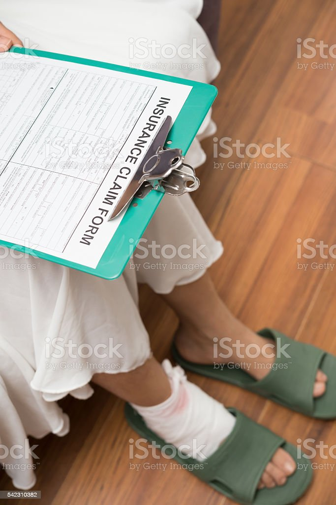 lady with hurted foot about to fill insurance claim form stock photo