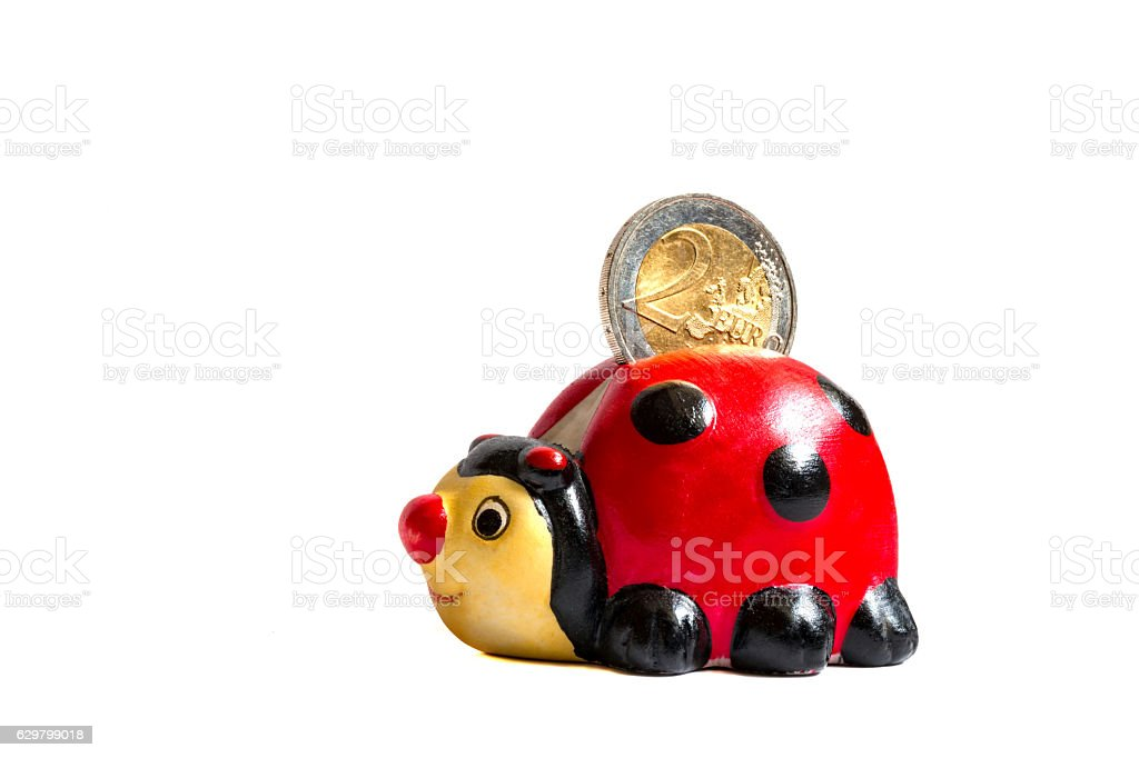 Ladybug savings box with two euro coin in it stock photo