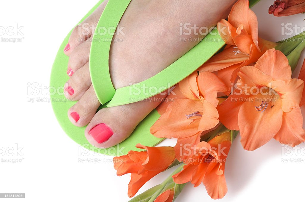 Lady's foot with painted toe nails and gladiola flower royalty-free stock photo