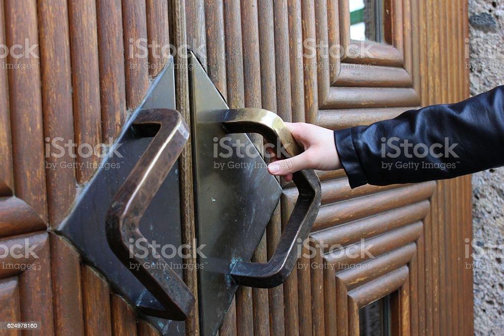 Lady's hand opening heavy bronze door stock photo