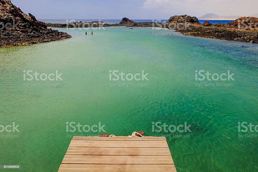 Lagoon with unknown persons and boat on the island Lobos. stock photo