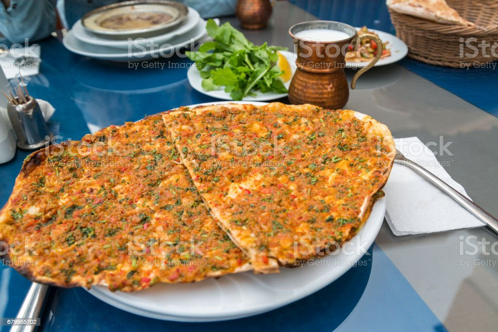Lahmacun (turksih pizza) on the talbe with ayran and grrenery stock photo
