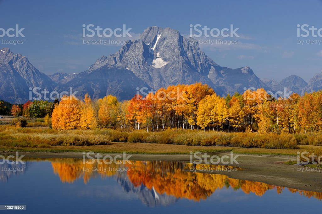 Lake and Autumn Forest Against Mountains royalty-free stock photo