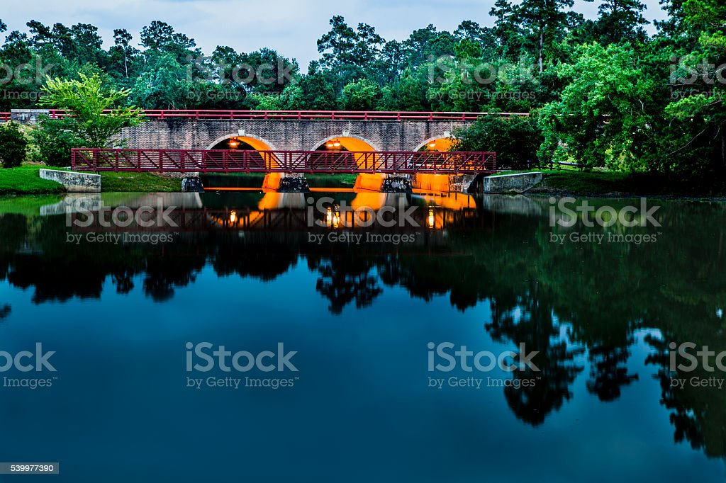 Lake and bridge in park setting. Tree reflection in pond. stock photo