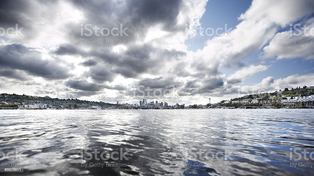 Lake and clouds with cityscape in background stock photo