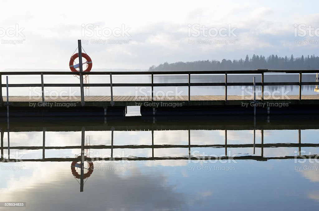 lake and wooden jetty in fog stock photo