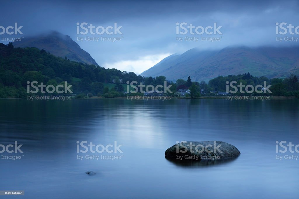 Lake at Dawn with Rolling Green Hills in Background stock photo