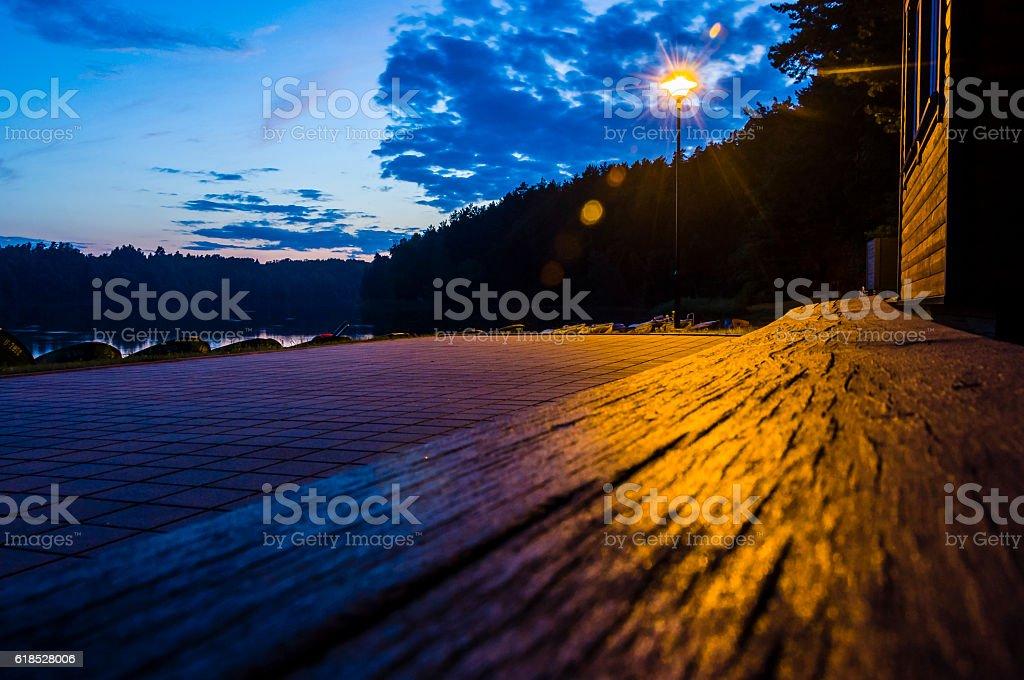 Lake beach, bench, sidewalk at night. Street lantern. Late sunset. stock photo
