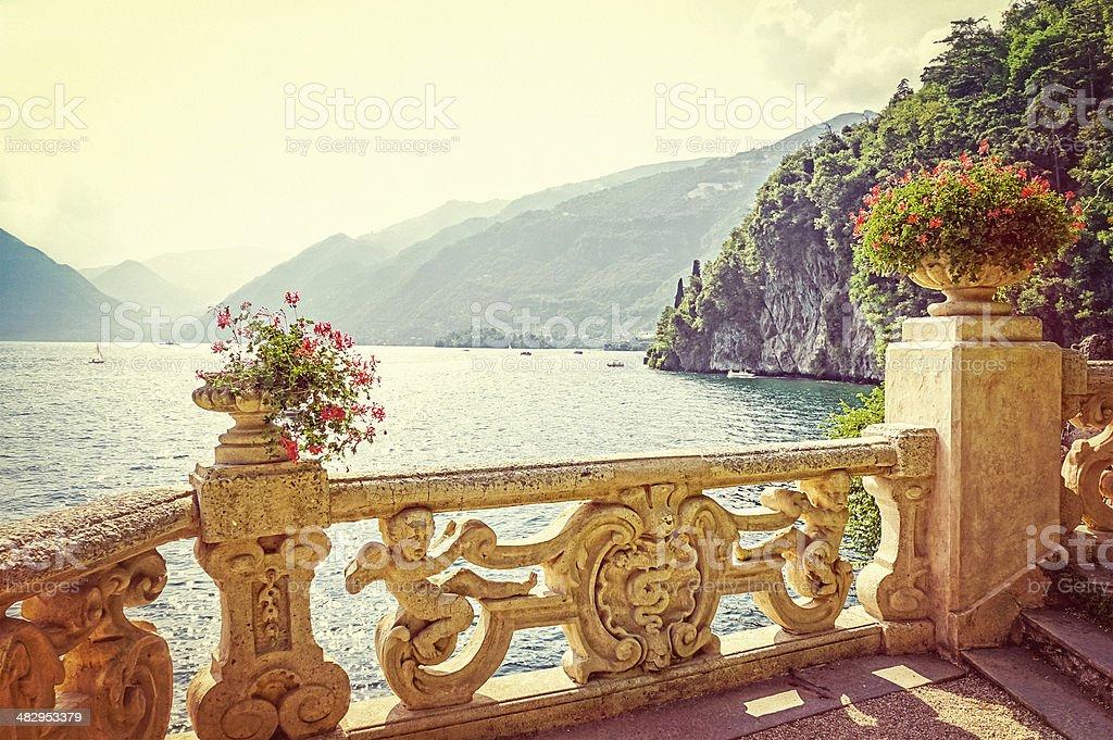 Lake Como, old decorated balcony, lake mountain view, sunset, retro stock photo