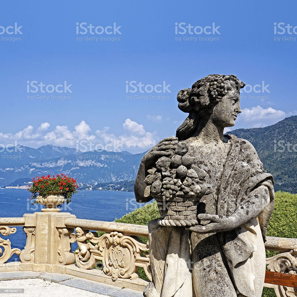 Lake Como, old sculpture, woman carrying fruits basket, lake view stock photo