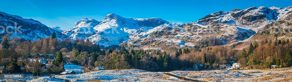 Lake District idyllic winter scene country village snowy mountains panorama stock photo