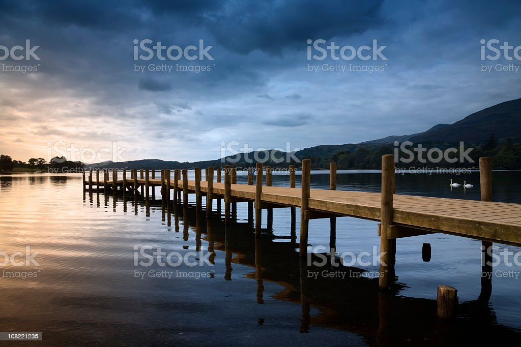 Lake Dock at Sunset with Stormy Sky stock photo