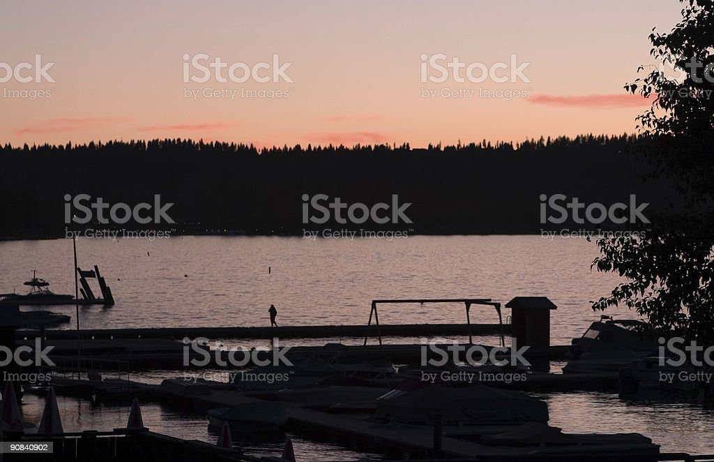 Lake dock in silhouette at sunset with forest stock photo