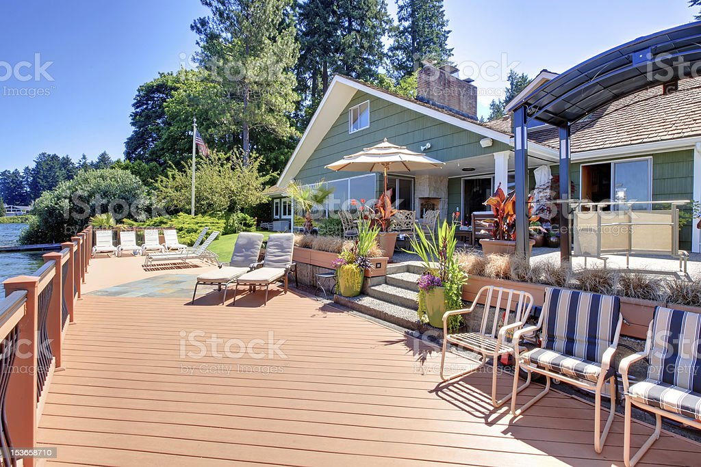 Lake fron house with large deck and outdoor living areas. stock photo