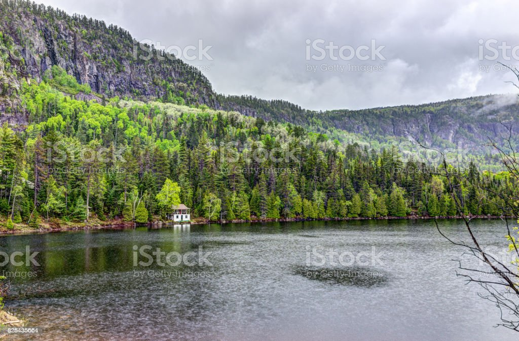Lake house in summer landscape by water during rainy cloudy day in Quebec, Canada stock photo