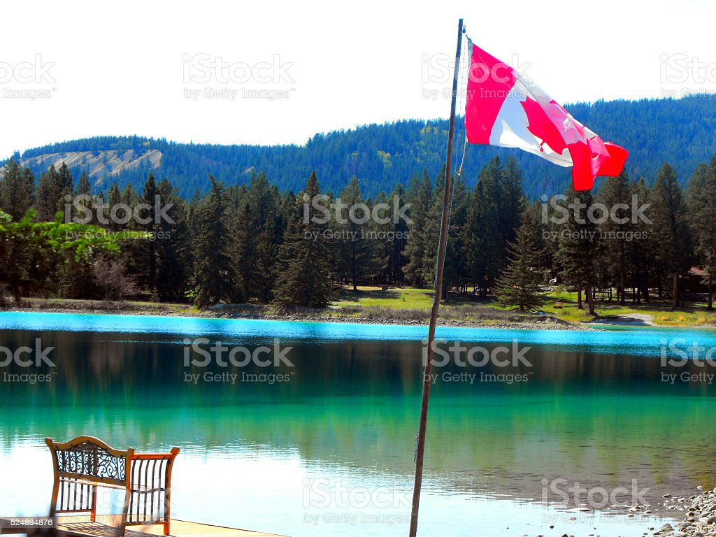Lake in Jasper, the Rocky Mountains with a Canadian Flag stock photo