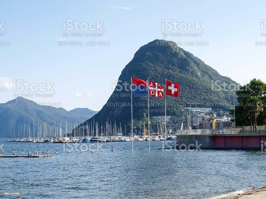 Lake Lugano, Monte San Salvatore ,and the flags of Switzerland, stock photo