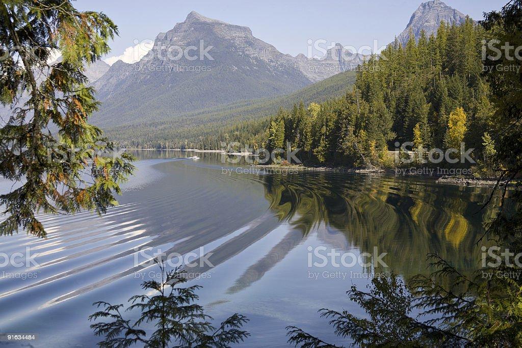 Lake McDonald boat wake effect on reflection stock photo